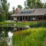 Stocked pond and dining hall building at Healing Waters Lodge